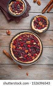 Autumn cranberries and pecan pies or tarts on wooden background, top view. Homemade seasonal pastry for Thanksgiving and autumn holidays.
