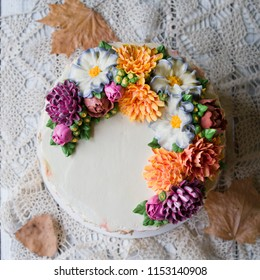 Autumn cream cake decorated with buttercream flowers (chrysanthemums) on white wooden  background with lace fabric. Close up, top view