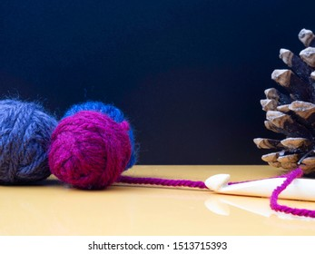 Autumn crochet image with bamboo crochet hook, balls of wool and a pine cone on a table. Room for text on a dark background.