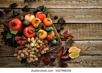 Autumn crop fruits. Autumn background with fall leaves, red apples and grapes. Fall harvest on aged wood with copy space. Mockup for seasonal offers, top view. Vintage style.