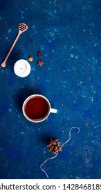 Autumn cup of tea with a spoon for honey, a candle, cinnamon and star anise on a dark blue background. Autumn layout, top view, flat lay
