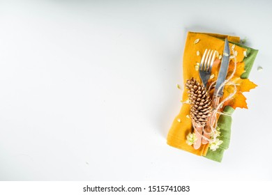Autumn cutlery background. Fall card background for menu or invitation, banner format. With fork, knife, napkins, pumpkin, plate, multicolored leaves. On white table, top view copy space