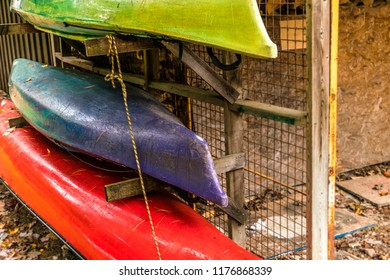 Autumn day at a cottage, canoe and kayak stacked on wooden rack for storage.