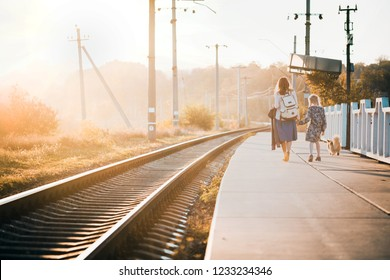 autumn day. mother and daughter are walking along the train waiting for the train