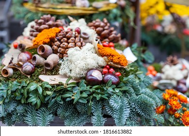 Autumn decor, composition with seasonal flowers and fir branches displayed for sale in a flower shop. Shallow depth of field, selective focus
