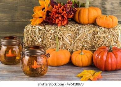 Autumn decor with natural straw bale, pumpkins, candle lights, flowers.