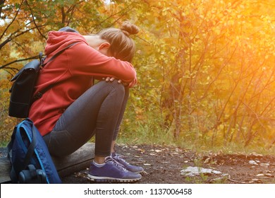 Autumn depression. Chandra. Children don't want to go to school. Despair. Hopelessness. Hopelessness. The girl sits, covering her face with her hands against the autumn forest. Photo with free space