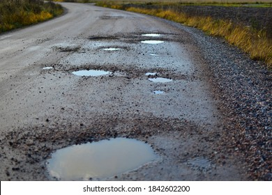 Autumn dirty gravel road with potholes. It has some surface damage, needs maintenance, hole patching, dust binding and dragging. The cost of maintaining gravel roads, is expensive and time consuming.