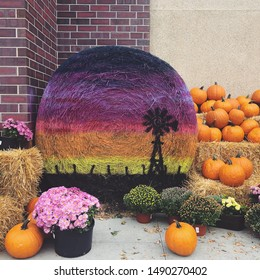 Autumn display of pumpkins, mums and roll of hay spray painted with farm scene outside of store