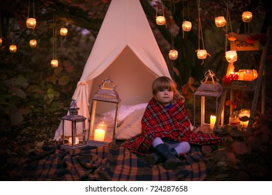 autumn evening forest with lights and baby girl covered with warm plaid background