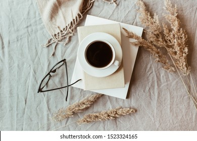 Autumn, fall composition. A cup of coffee lying on the grey linen bed with beige warm blanket, books, glasses and reeds. Lifestyle, still life concept. Flat lay, top view.