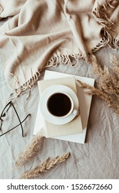 Autumn, fall composition. A cup of coffee lying on the grey linen bed with beige warm blanket, books, glasses and reeds. Lifestyle, hygge concept. Flat lay, top view.
