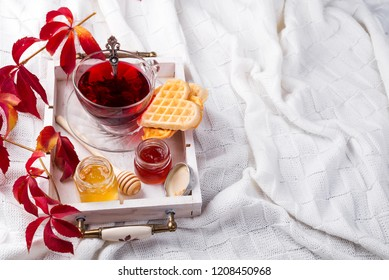 autumn fall concept with knitted blanket and hot tea with waffer, jam, honey on wooden tray on te bed, autumn leaf and candle. Copy space