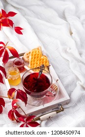 autumn fall concept with knitted blanket and hot tea with waffer, jam, honey on wooden tray on te bed, autumn leaf and candle