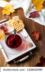 autumn fall concept with knitted blanket and hot tea with waffer, jam, honey on wooden tray on wooden background, autumn leaf . Copy space