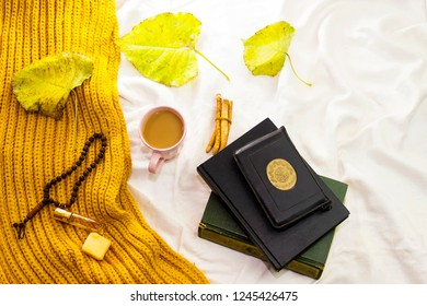 autumn fall concept for muslim, holy book of muslims and rosary, siwak, perfume on bed