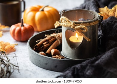 Autumn or fall concept with a romantic shabby chic lantern, aromatic spices, autumnal leaves and pumpkins at the background. Fall home decoration