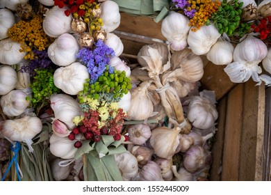 Autumn or fall display with fresh garlic bulbs and bunches of colorful flowers in alternating rows conceptual of the seasons