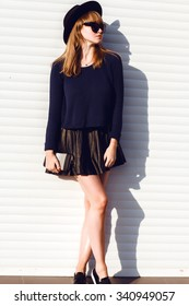 autumn fall fashion image of american trill woman posing on white wall,wear trendy urban street clothes,leather skirt,black hat,warm blue sweater.street fashion clothes outdoor,accessory fashion,warm
