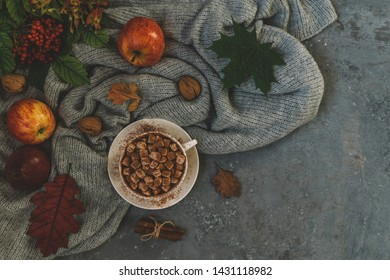 Autumn, fall leaves, hot cup of coffee with marshmallow and a warm scarf on wooden table background. Seasonal, morning coffee, relaxing and still life concept. Toned image. Top view, copy space.