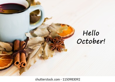 Autumn, fall leaves, hot steaming cup of glint wine on wooden table background. Seasonal, autumnal hot wine, Autumn relaxing and still life concept. Top view with text hello october.