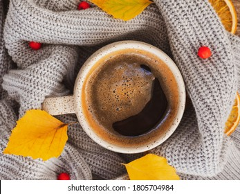 Autumn or Fall morning coffee. Fall yellow leaves, red Rowan berries, hot steaming mug of black coffee and a cozy grey sweater as background. Sunday relaxing, autumn mood and still life concept.