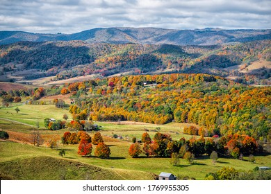 Autumn fall orange red colorful trees forest and farm houses buildings on rolling hills aerial above high angle view landscape in Monterey and Blue Grass, Highland County, Virginia
