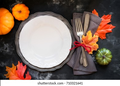 Autumn or Fall table place setting with vintage silverware decorated with autumnal leaves and decorative pumpkins with a plate on rustic wooden background for Thanksgiving Day