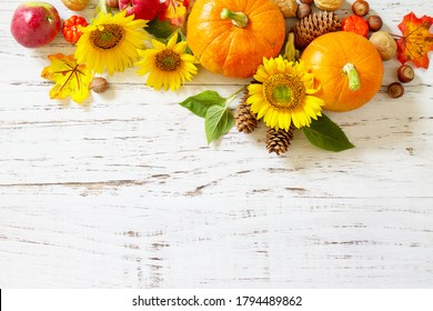 Autumn, fall, Thanksgiving concept. Pumpkins, sunflowers, apples and fallen leaves on rustic wooden table. Copy space.