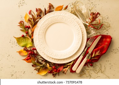 Autumn (fall) or thanksgiving table setting design captured from above (top view, flat lay). Empty white plate, glass, cutlery and decorations (colorful leaves). Background with free text space.