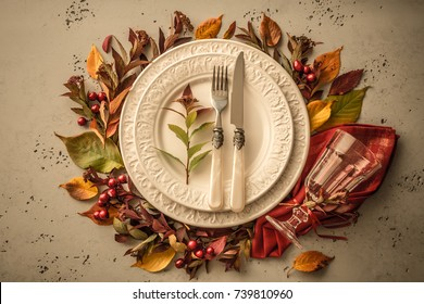 Autumn (fall) or thanksgiving table setting design captured from above (top view, flat lay). White plate, glass, cutlery and decorations (colorful leaves). Dark moody light.