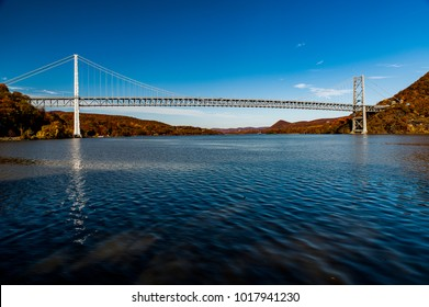 An autumn / fall view of the graceful historic Bear Mountain suspension bridge across the Hudson River in New York.