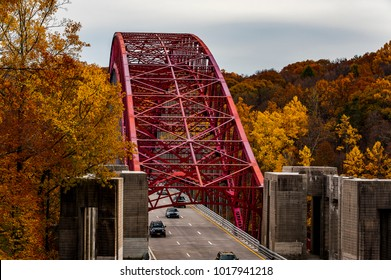 An autumn / fall view of a red hued steel arch bridge that carries the Taconic Parkway over the New Croton Reservoir in Westchester County, New York.