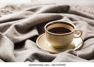 Autumn, fall, winter home decor in scandinavian, hygge style. Seasonal composition with cup of coffee, warm woolen scarf, soft plaid on a rustic wooden table.