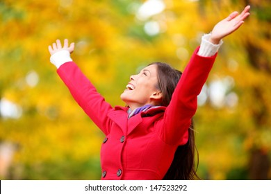 Autumn / fall woman happy in free freedom pose with arms raised up towards the sky with smiling cheerful, elated expression of happiness. Beautiful girl in colorful forest foliage outdoor.