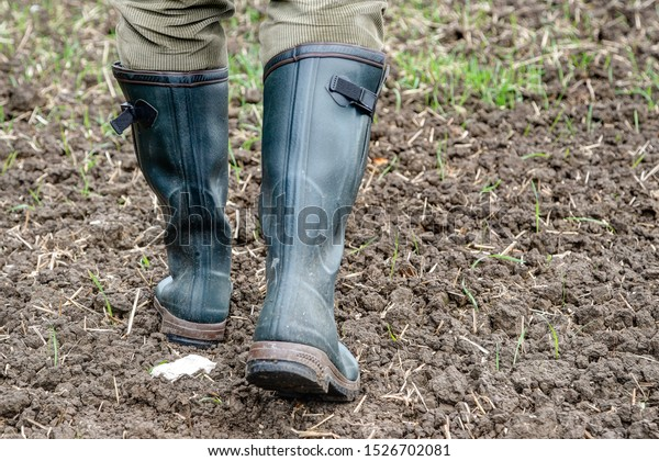 In autumn, a farmer goes with his green rubber boots over the freshly sown field.