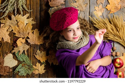 Autumn fashion accessories concept. Fashion trend fall season. Child lay wooden background fallen leaves top view. Knitted accessory fashion detail. Fashion kid girl wear knitted hat beret and scarf.