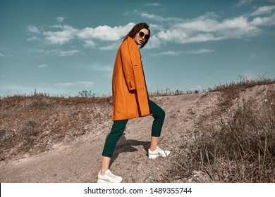 Autumn fashion. Beautiful attracrive young woman in bright autumn look. Orange trendy coat and pants and fashion sunglasses.