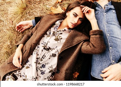 Autumn fashion. Beautiful fashionable lady lying on the shoulder of her partner. Yellowed autumn grass and leaves.