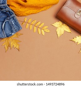 Autumn Fashion Concept. Brown leather women bag, orange knitted sweater, blue jeans, golden autumn leaf on brown background top view flat lay copy space. Fashionable women's accessories Female Clothes