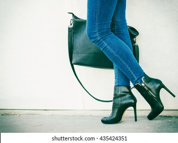 Autumn fashion outfit. Fashionable woman long legs in denim pants black stylish high heels shoes and handbag outdoor on city street