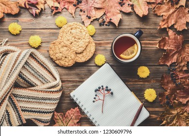 Autumn fashion seasonal concept Scandinavian knitted scarf cup hot black tea coffee homemade oatmeal cookies Fall fallen maple leaves on wooden table with notebook pen Flat lay Top view vintage style.
