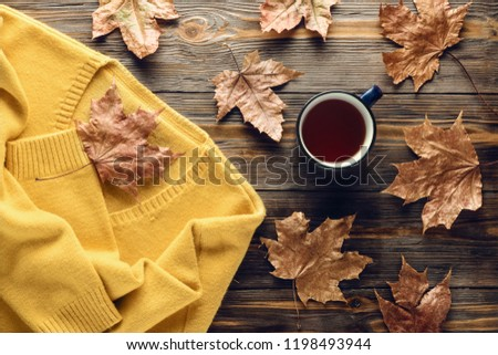 Autumn fashion seasonal concept, yellow warm soft comfortable sweater cardigan cup hot black tea coffee Fall fallen maple leaves on wooden table Flat lay Top view vintage style