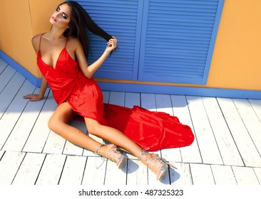 Autumn Fashion Shopping Sexy Model Girl full length Portrait.Beauty Woman with hight heels shoes and long red dress laying on the wooden floor. Blowing brunette hair, high hills. Shopper. Sales,cool