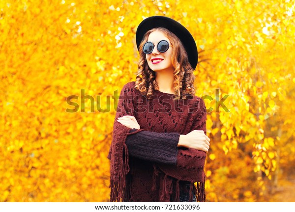 autumn fashion smiling woman in black round hat, knitted poncho on a yellow leaves background