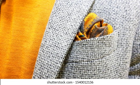 autumn fashion style with yellow and orange polo combined with a pocket square in the same color with a light gray wool blazer