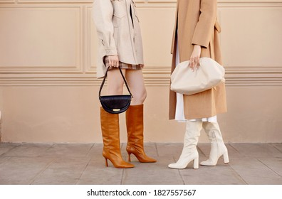 Autumn fashion two women in trendy clothes coat, high boots, bags . Street style outfit