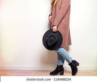 Autumn fashion. Woman in beige coat and stylish boots holding a hat in hand.