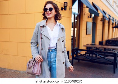 Autumn fashionable image of cute young woman with short hairs and candid smile.  Trendy coat, denim jeans.    Student female posing inver yellow wall. Outdoor .