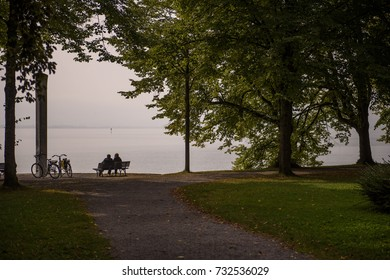 Autumn feel good photo with a romantic vibe taken in a park on the side of a lake capturing the silhouette of a couple sitting on a bench, with two bicycles and trees around them. Germany in October.